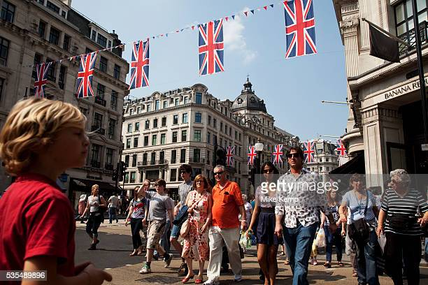 People cross the busy shopping street under Royal Wedding Union flags on Regent Street London A display of 200 giant Union Jack Flags run all the way...