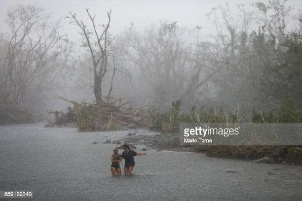 People cross the Espiritu Santo river during heavy afternoon rains more than two weeks after Hurricane Maria hit the island on October 8 2017 in...