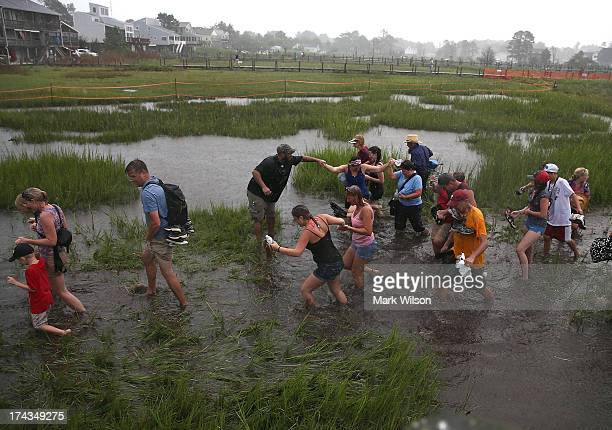 People cross the marsh in the pouring rain after watching wild ponies during their annual swim from Assateague Island to Chincoteague on July 24 2013...