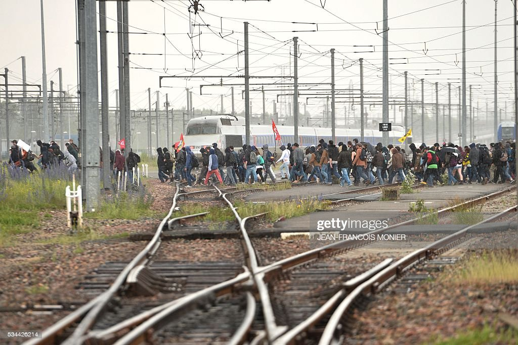 People cross the railway lines during a protest against the government's labour market reforms in Rennes, on May 26, 2016. The French government's labour market proposals, which are designed to make it easier for companies to hire and fire, have sparked a series of nationwide protests and strikes over the past three months.