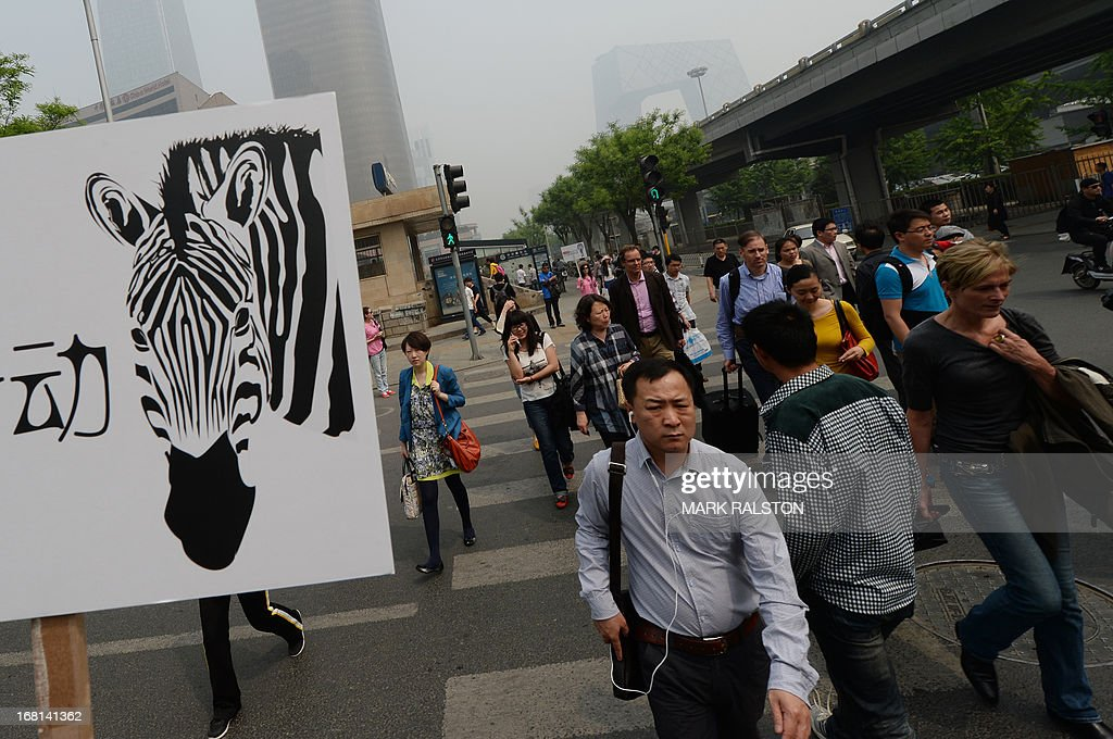 People cross the road during a road safety campaign as the government announces its first ever fine (USD 1.50) for jaywalking in Beijing on May 6, 2013. China's roads are highly dangerous, with traffic laws and safety widely flouted, and truck drivers typically overworked. Last year more than 62,000 people officially died in traffic accidents but a recent World Heath Organization report suggested the rate was more than double that. AFP PHOTO/Mark RALSTON