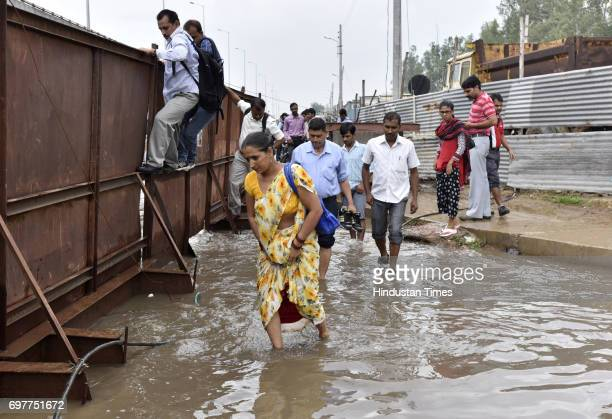 People cross the road through the waterlogging at Hero Honda Chowk after heavy rainfall lashed Delhi and NCR on June 19 2017 in Gurgaon India With...