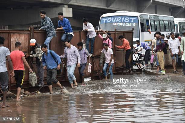 People cross the road through the waterlogging at Hero Honda Chowk after the heavy rainfall lashed Delhi and NCR on June 19 2017 in Gurgaon India...