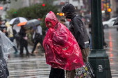 People cross the street during a heavy rain storm on October 7 2013 in New York City A severe thunderstorm brought rain potential hail and a tornado...