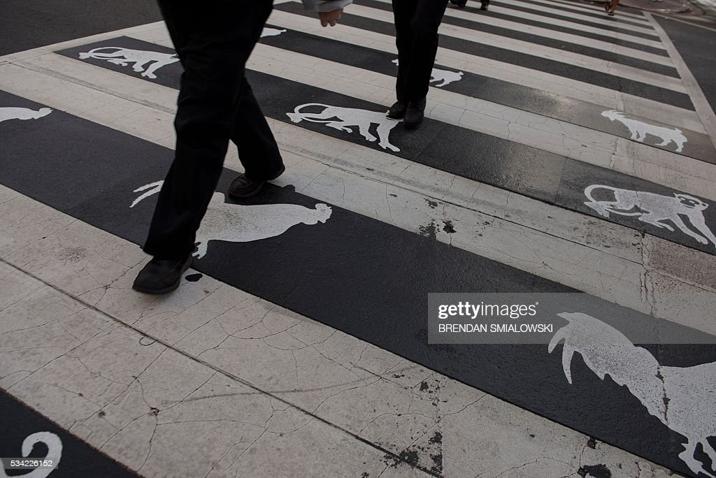People cross the street in Chinatown May 25, 2016 in Washington, DC. / AFP / Brendan Smialowski