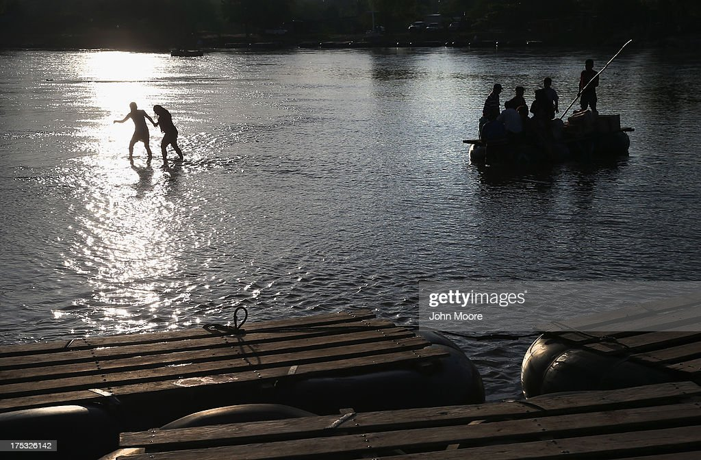 People cross the Suchiate River from Guatemala into Mexico on August 2, 2013 in Ciudad Hidalgo, Chiapas, Mexico. Thousands of undocumeted Central Americans pass illegally through Mexico, many of them immigrants on the first leg of their long and perilous journey north to the United States.