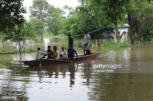 People cross water on boat as flood like situation is created in village Pipalkhedi after three sluice gates of the Halali dam some 55KM away from...