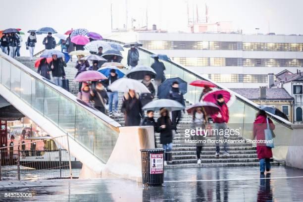 People crossing Ponte della Costituzione in a rainy day