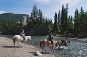 People Crossing Spray River on Horseback