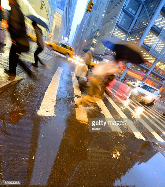 People crossing street on rain wet zebra x-ing, NYC