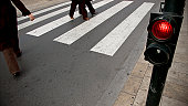 People crossing the road at red light on pedestrian crossing
