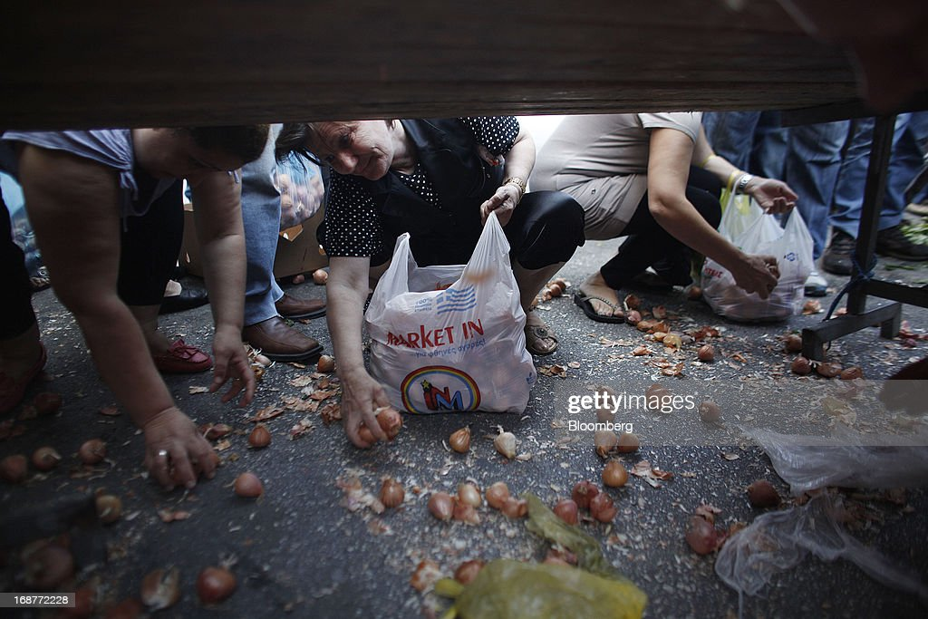 People crouch to collect free vegetables from the ground during a handout of leftover food by striking street vendors in Athens, Greece, on Wednesday, May 15, 2013. Greece's plans to return to international bond markets next year reflect the government's confidence it can draw a line under the country's debt crisis although the cost of borrowing suggests that might be premature. Photographer: Kostas Tsironis/Bloomberg via Getty Images