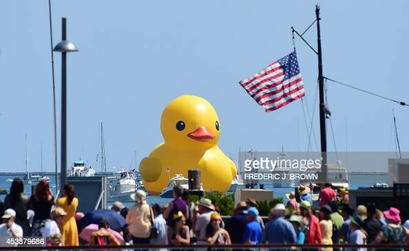 People crowd a pier to watch as the sixstory tall 'Rubber Duck' by Dutch artist Florentijn Hofman leads a procession of Tall Ships into Los Angeles...