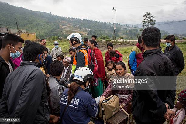 People crowd around a small table giving medical checks and tending to minor injuries by medical staff from a China search and rescue team in a field...