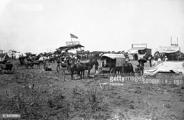 People crowd around an auction in progress at the lumber company booth Many hold umbrellas for sun Temporary bank buildings and the beginnings of a...
