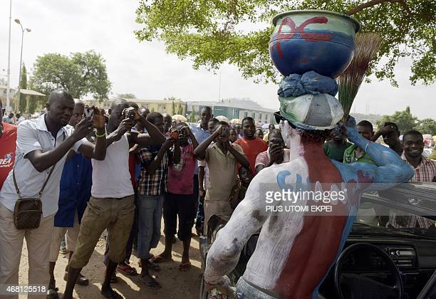 People crowd around to take pictures of a man wearing glasses and body paint adorned with the logo of Nigeria's main opposition All Progressives...
