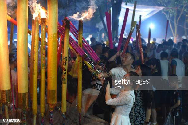 People crowd at Yuhu Temple to burn incense and worship Guanyin the Buddhist goddess of mercy ahead of Guanyin's birthday at Yuqing County on July 11...