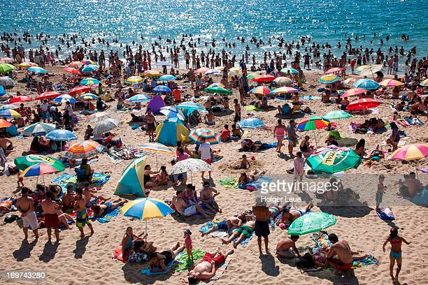 People crowd beach on a sunny Sunday afternoon