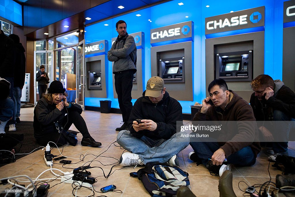 People crowd into a Chase Bank ATM kiosk to charge phones and laptops at 40th Street and 3rd Avenue, one block north of where power has gone out, on October 31, 2012 in New York, United States. 'This is the modern campfire,' one man mentioned to another man. Businesses across the eastern seaboard are attempting to return to normal operations as clean-up from Hurricane Sandy continues.