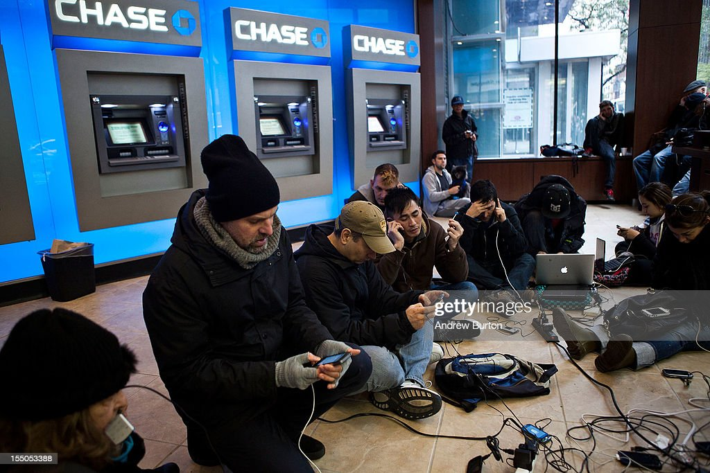 People crowd into a Chase Bank ATM kiosk to charge phones and laptops at 40th Street and 3rd Avenue, one block north of where power has gone out, on October 31, 2012 in New York City. 'This is the modern campfire,' one man said. Businesses and residents across the eastern seaboard are attempting to return to their daily lives and normal operations as clean-up from Hurricane Sandy continues.