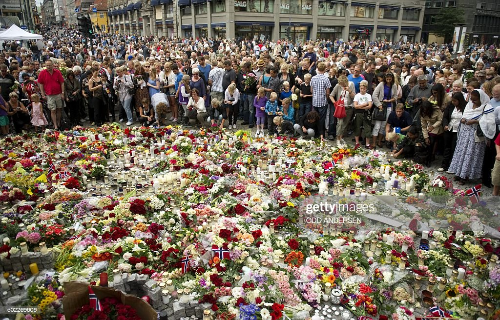 People crowd on July 24 2011 in Oslo around a flower tribute to the victims of a bomb explosion which ripped through government buildings and the...