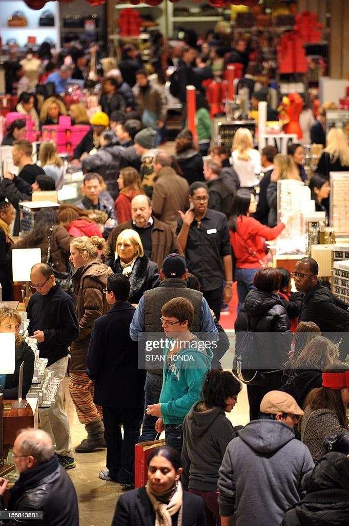 People crowd the first floor of Macy's department store as they open at midnight (0500 GMT) on November 23, 2012 in New York to start the stores' 'Black Friday' shopping weekend. AFP PHOTO/Stan HONDA