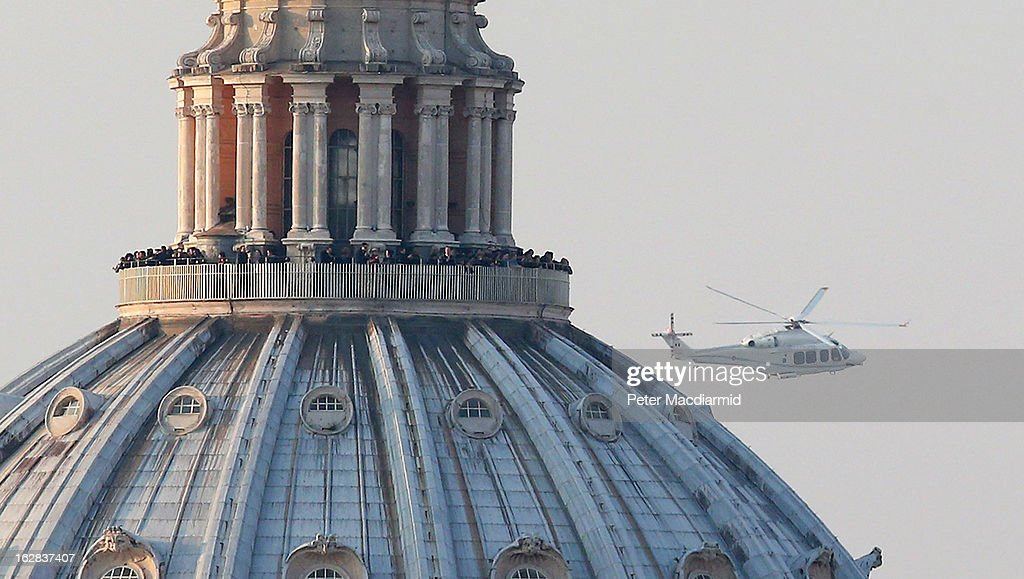 People crowd the gallery on top of St Peter's Basilica as a helicopter carrying Pope Benedict XVI passes by on its way out of Vatican City on February 28, 2013 in Rome, Italy. The Pontiff is flying to Castel Gandolfo where he will cease to be Pope at 8:00pm local time. Pope Benedict XVI has been the leader of the Catholic Church for eight years and is the first Pope to retire since 1415. He will stay at the Papal Summer residence of Castel Gandolfo until renovations are complete at a monastery in the grounds of the Vatican and will be known as Roman pontiff emeritus or pope emeritus.