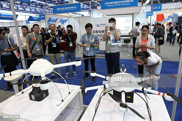 People crowd to view Unmanned Aerial Vehicle models exhibited on the Aviation Expo China 2015 at China National Convention Center on September 16...