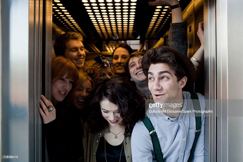 People crowding into elevator : Stock Photo