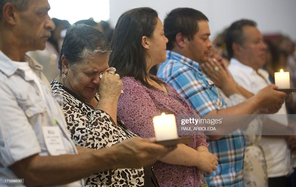 People cry next to the urns with the remains of their relatives disappeared during the Colombian civil war until recently, on June 21, 2013 in Medellin, Antioquia department, Colombia. In a ceremony, relatives of 36 victims received the remains of their loved ones, which were recently found in common graves due to information given by demobilized combatants of both, leftist guerrillas and right-wing paramilitary groups, in the framework of the country's peace process. AFP PHOTO/Raul ARBOLEDA