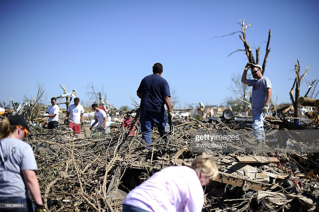 People cut trees felt on a tornado devastated home on May 22, 2013 in Moore, Oklahoma. As rescue efforts in Oklahoma wound down, residents turned to the daunting task of rebuilding a US heartland community shattered by a vast tornado that killed at least 24 people. The epic twister, two miles (three kilometers) across, flattened block after block of homes as it struck mid-afternoon on May 20, hurling cars through the air, downing power lines and setting off localized fires in a 45-minute rampage. AFP PHOTO/Jewel Samad