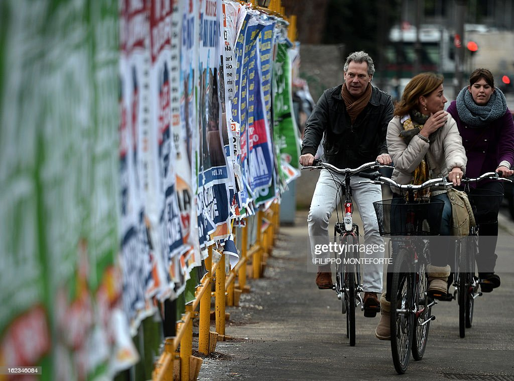 People cycle by electoral billboards in Castel Gandolfo, south of Rome on February 22, 2013. Italy held its final day of campaigning on February 22 ahead of crucial elections, as international investors warned an unclear outcome could shake the economy and set off shockwaves through the eurozone.