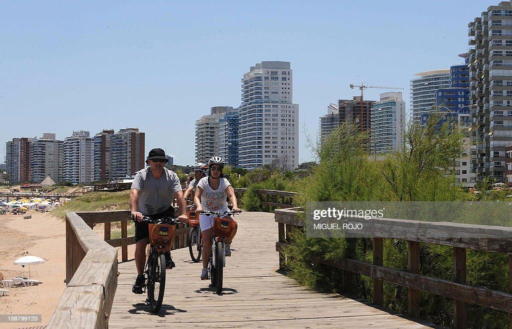 People cycle in Punta del Este, Maldonado, Uruguay on December 28, 2012. AFP PHOTO/Miguel ROJO