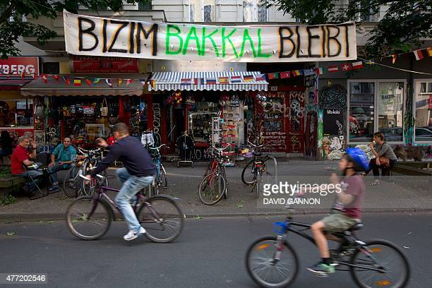 People cycle in the Wrangel Street in Berlin's Kreuzberg district opposite Ahmet Caliskan's fruit and vegetable shop Bizim Bakkal on June 12 2015...