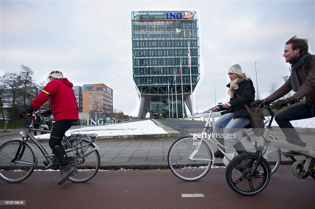 People cycle on February 13, 2013 in front of the headquarters of the Dutch banking and insurance group ING in Amsterdam. ING reported on February 13 a 32.5-percent plunge in net profit last year and said that it intended to cut 2,400 jobs in its operations in the Netherlands and Belgium. AFP PHOTO / ANP / EVERT ELZINGA - netherlands out -