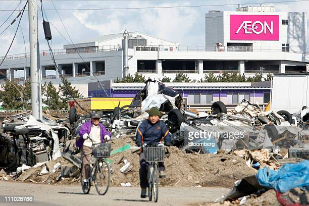 People cycle through the debris from the March 11 earthquake and tsunami near an Aeon Co shopping center in Tagajo City Miyagi Prefecture Japan on...