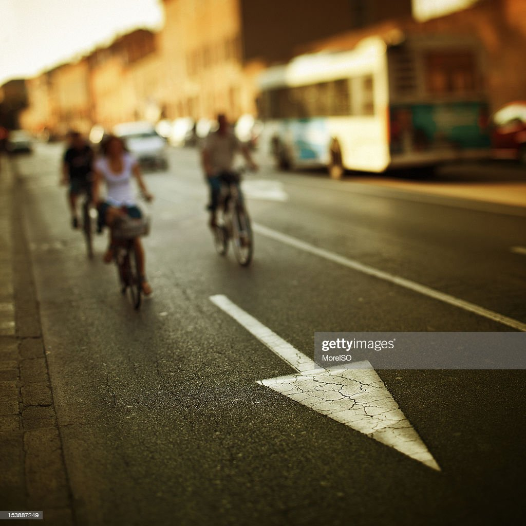 People Cycling in a City Street, Tilt Shift, Arrow Sign : Stock Photo