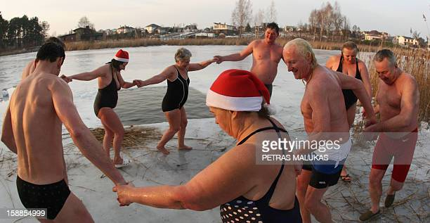 People dance after taking part in the traditional New Year's swimming at the Geluzis Lake on January 1 2013 in Vilnius Lithuania AFP PHOTO / PETRAS...