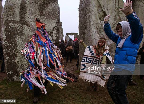 People dance as a man dressed in a rag costume plays an accordion as druids pagans and revellers gather hoping to see the sun rise as they take part...