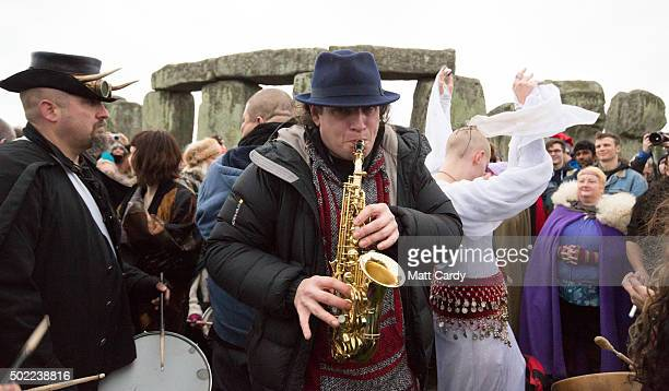 People dance as a man plays a saxaphone outside the stones as druids pagans and revellers gather at Stonehenge hoping to see the sun rise as they...