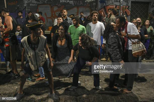 People dance as the Brazilian trio 'Jazz de Boteco' plays on the street in front of the 'Bar do Nanam' bar in Rio de Janeiro Brazil on August 24 2017...