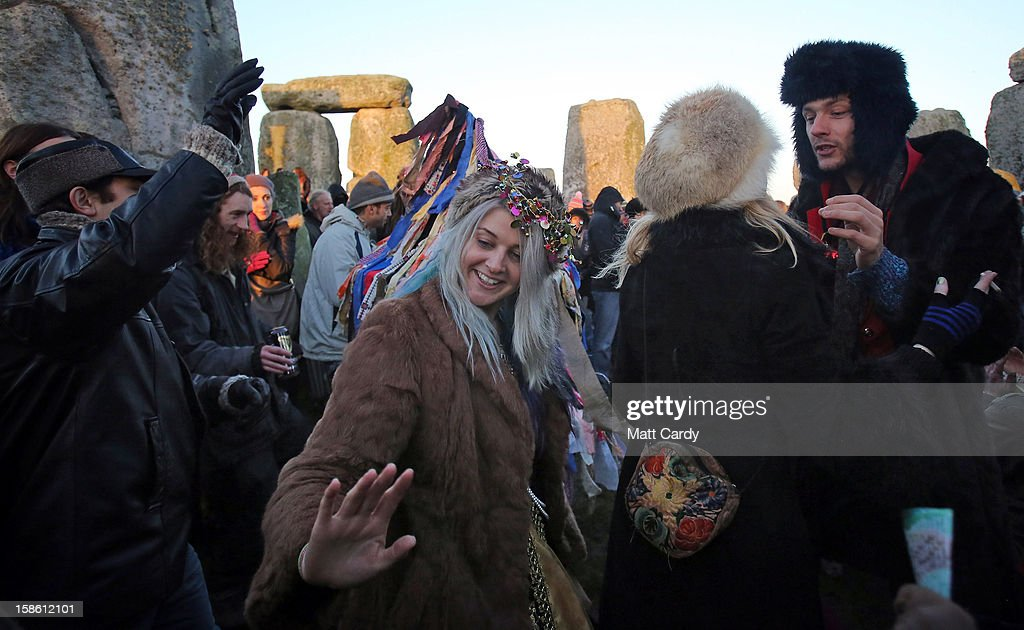 People dance as the sun rises, as druids, pagans and revellers, celebrate the winter solstice at Stonehenge on December 21, 2012 in Wiltshire, England. Predictions that the world will end today as it marks the end of a 5,125-year-long cycle in the ancient Maya calendar, encouraged a larger than normal crowd to gather at the famous historic stone circle to celebrate the sunrise closest to the Winter Solstice, the shortest day of the year.