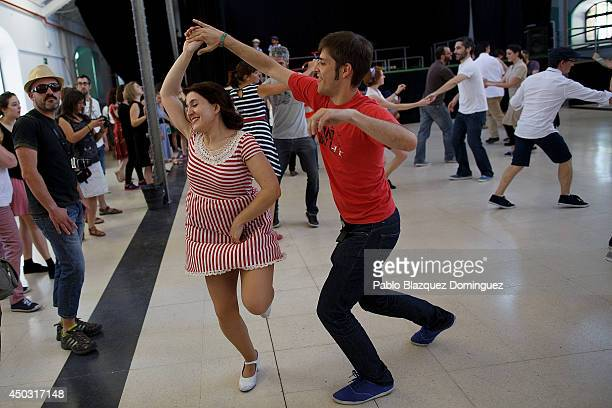 People dance during a Lindy Hop session dafter the Tweed Ride Madrid on June 8 2014 in Madrid Spain Cyclist dressed in tweed and riding vintage old...