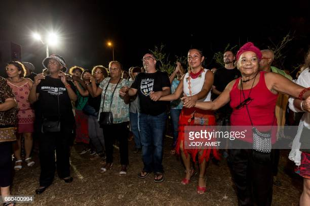 People dance during a Native Amerindians' Sampula party within a protest gathering at a blockade on March 29 2017 in Cayenne French Overseas...