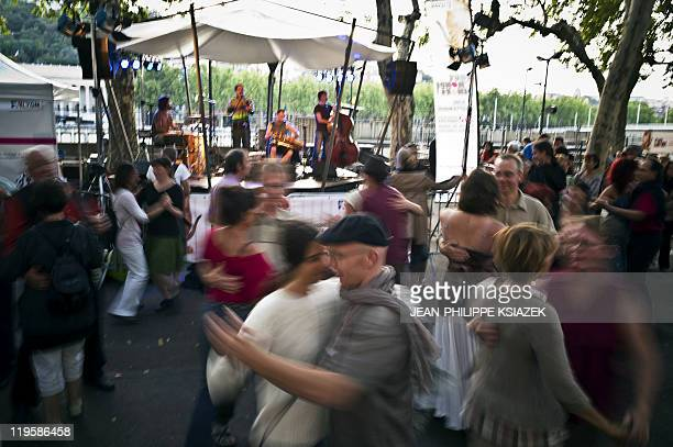 People dance during a socalled French 'bal populaire' a hop or local dance to celebrate the Bastille day on July 14 2011 on the banks of the Saone...