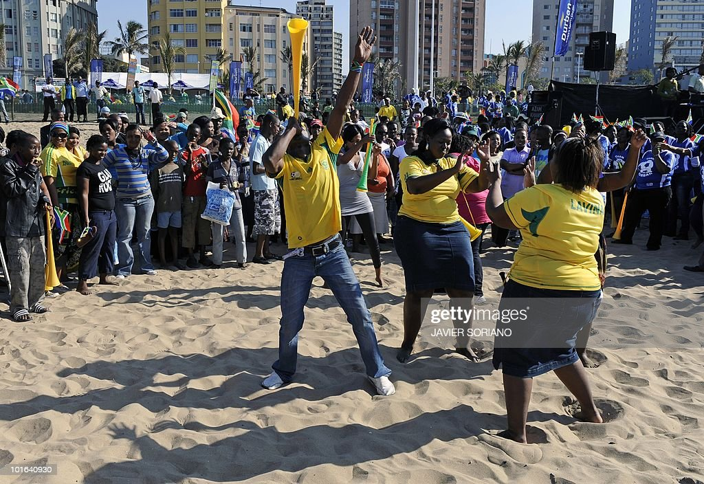People dance during a street party to celebrate five days before the beginning of the 2010 World Cup football tournament at a Durban beach on June 5, 2010. Durban is one of the nine cities hosting matches of the tournament from June 11 to July 11 in South Africa.