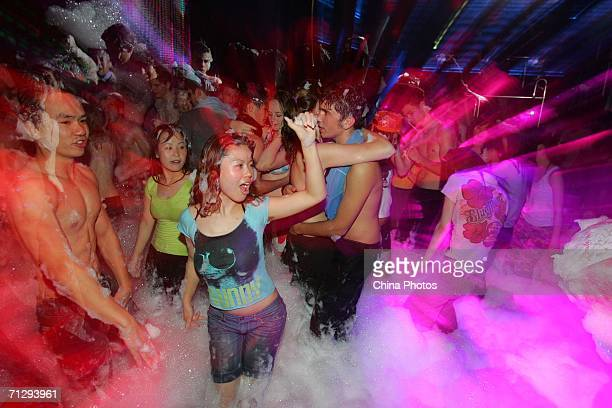 People dance during the Foam Party at the Rojam Disco on June 24 2006 in Shanghai China Foam Parties during which participants are lathered up with...