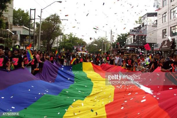 People dance holding a huge rainbow flag during the Gay Pride Parade in Guadalajara Jalisco state Mexico on June 20 2015 AFP/PHOTO HECTOR GUERRERO