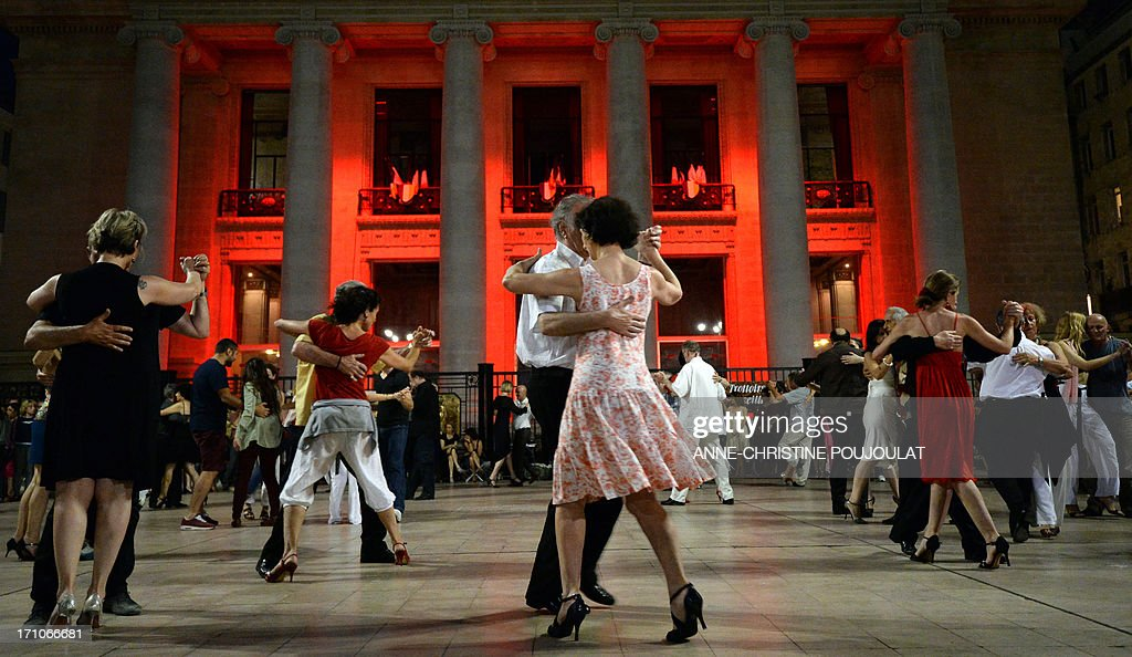 People dance tango in front of the opera house in Marseille, southern France, on June 21, 2013 during the 32nd edition of the annual music event 'La Fete de la Musique' . The event takes place across the streets of France, with thousands of musicians performing for one of the nation's most popular festivals celebrating rythm and sound. AFP PHOTO / ANNE-CHRISTINE POUJOULAT