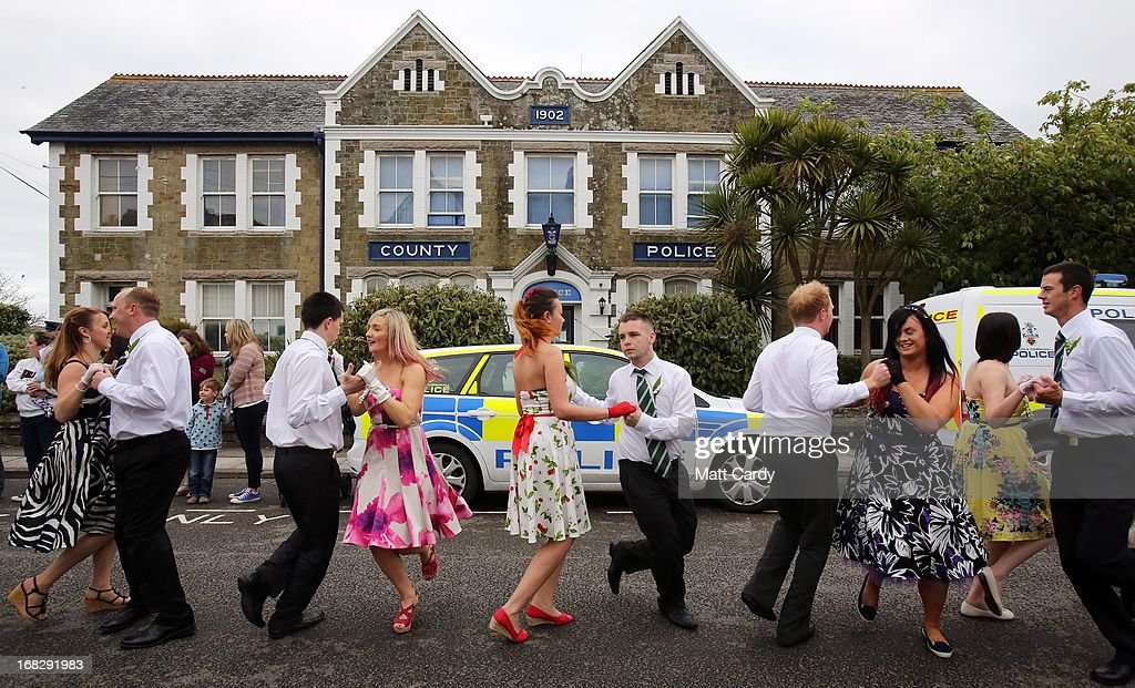People dance through the town as they take part in the Early Morning Dance as they celebrate Helston Flora Day on May 8, 2013 in Cornwall, England. The annual Flora Dance, also known as the Furry Dance, is one of the UK's oldest customs still practised today and is said to be a celebration of the passing of Winter and the arrival of Spring. A series of dances take place throughout the day, beginning at 7am, all over the Cornish town and even in and out of private houses and shops. However the highlight is the midday dance which was traditionally the dance of the gentry in the town and is why men still wear top hats and tails while the women dance in their finest dresses.
